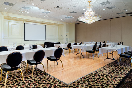Empty hotel conference meeting or event room provides space for business meetings, conferences, speakers, or events. Tables and chairs set up to veiw projection screen.